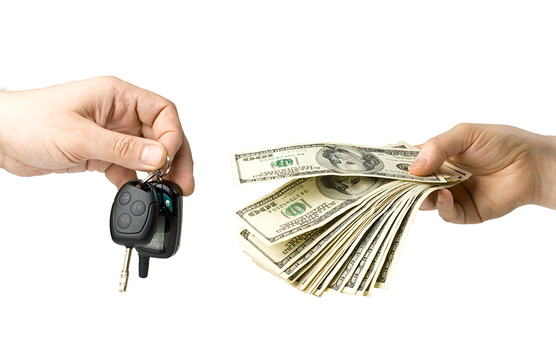 Hand with money and car keys on a white background